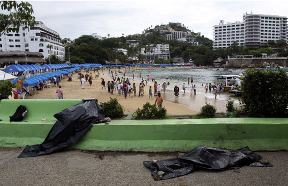 2 covered bodies on a street facing a beach, Acapulco, Mexico. Photo courtesy of Reuters