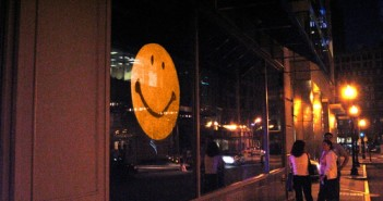 Brian Knep, Big Smile, 2003. An archetypal smiley face blinks, looks at viewers, and smiles only when no one is looking directly at it. Viewers get a glimpse of the smile as they look away, but when they look back the smiley no longer smiles. The piece is mounted on a gallery window and can be seen from both sides, but interacts only with visitors outside the gallery.