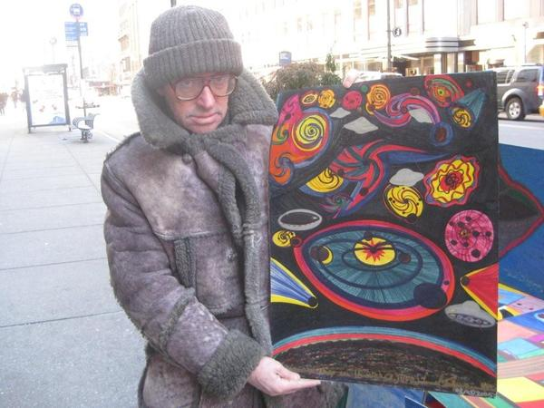 Ionel Talpazan stands with his work. Ionel sells his work in front of the fair every year. UFOs are the main subject. He's been covered by Raw Vision magazine and CNN; his work was in the movie K-PAX.