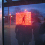 An LED piece by Jim Campbell, reflected in the windows of Axiom Gallery.
