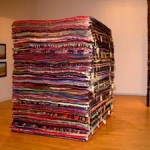 A stack of hundreds of blankets by Marie Watt.