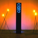 AIDS-3D, OMG Obelisk, MDF, electroluminescent wire, steel, hot glue, acrylic paint and fire, 2007.