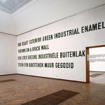 Installation view of Lawrence Weiner's One Quart Exterior Green Industrial Enamel Thrown on a Brick Wall.