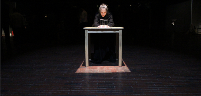 Edge Durational performance by Marilyn Arsem Near Death Performance Art Experience Cyclorama, Boston, MA April 2013 Photo by Phil Fryer