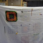 """Fields holds up one of the cross-stitched panels from her """"Circus Project"""""""