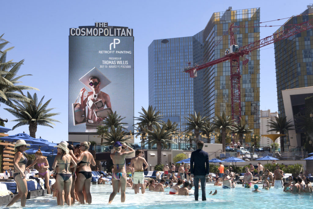 Thomas Willis standing with the Retrofit Painting of Las Vegas sign at Cosmopolitan of Las Vegas on the Las Vegas Strip, summer 2015. Photo by Mikayla Whitmore.