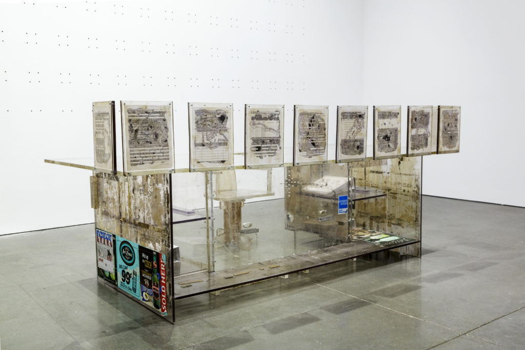 Nari Ward, Naturalization Drawing Table, 2004. Plexiglas, crenelation table, and INS naturalization application, two parts: table 45 x 51 x 99 inches; chair 34 x 22 x 21 inches. Courtesy the artist; Galleria Continua, San Gimignano, Beijing, Les Moulins, and Havana; and Lehmann Maupin, New York and Hong Kong. Installation view, Nari Ward: Sun Splashed, Institute of Contemporary Art Boston, 2017 Photo by John Kennard. © Nari Ward