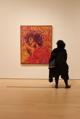"A visitor stares transfixed with Wadsworth Jarrell's ""Revolutionary (Angela Davis)"""